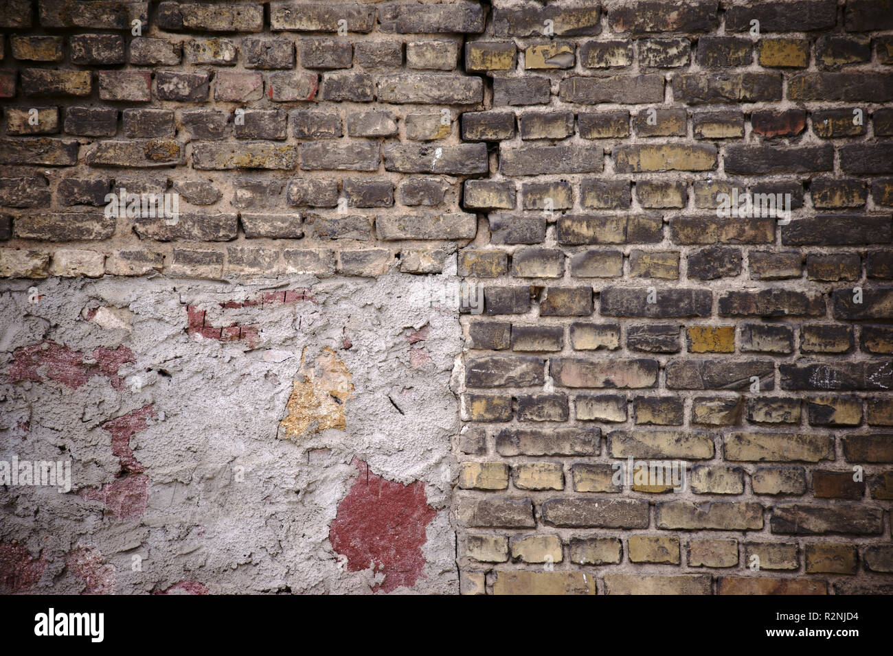 Rustic wall in danger of collapse out of staggered and broken bricks with a crack and repair points, - Stock Image