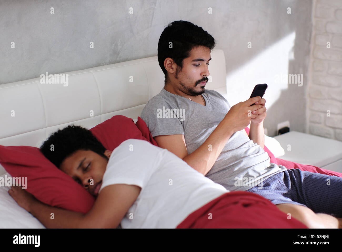 Homosexual couple, gay people. Man being unfaithful and texting with lover while his partner is sleeping in bed - Stock Image