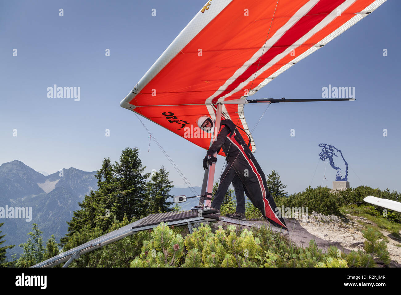 Hang glider in front of artwork Adams hand from Angerer the Younger one on the Rauschberg, Ruhpolding, Chiemgau Alps, Chiemgau, Upper Bavaria, Bavaria, southern Germany, Germany, Europe - Stock Image
