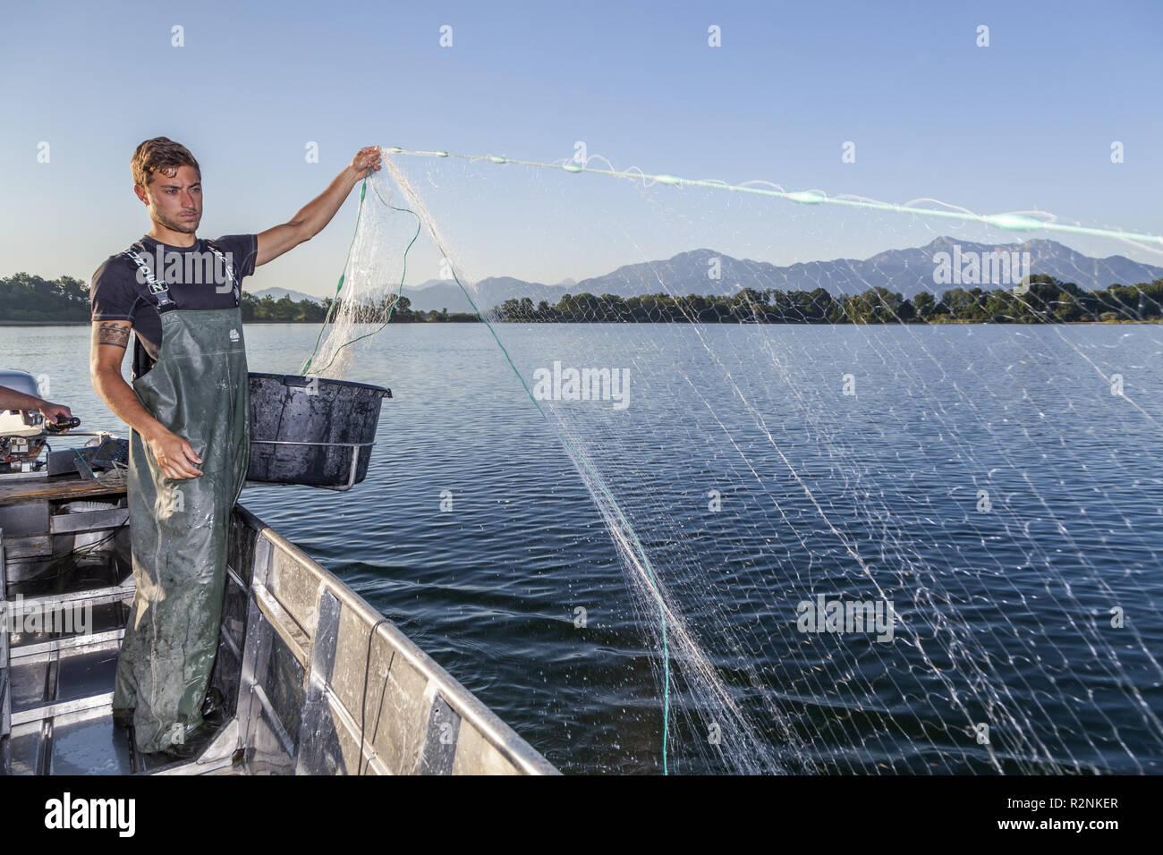 Fishermen Thomas and Florian Lex from Fraueninsel laying nets, Frauenchiemsee, Chiemgau, Upper Bavaria, Bavaria, Southern Germany, Germany, Europe - Stock Image