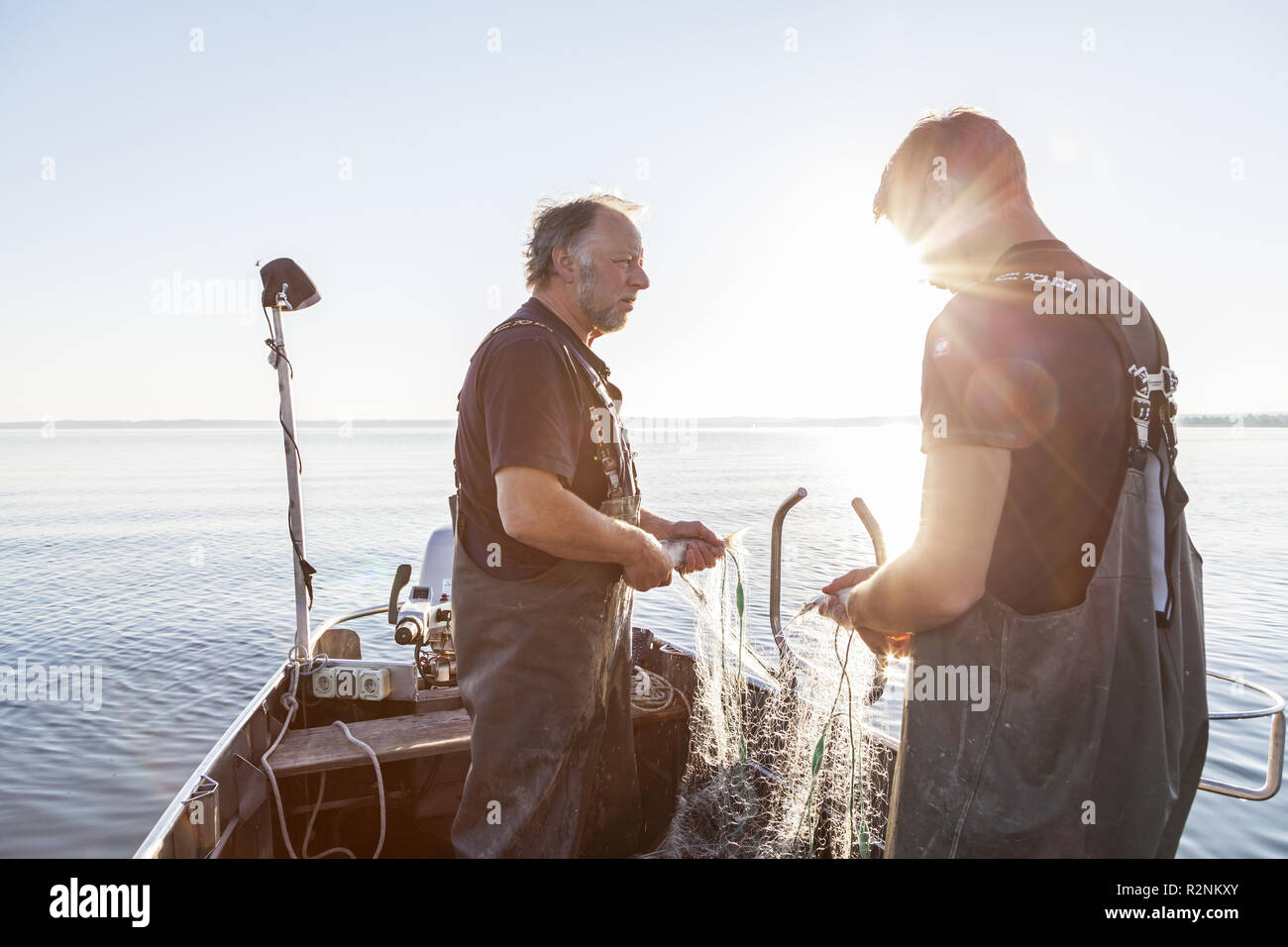 Fishermen Thomas and Florian Lex of the Fraueninsel catching the nets, Frauenchiemsee, Chiemsee, Chiemgau, Upper Bavaria, Bavaria, southern Germany, Germany, Europe - Stock Image