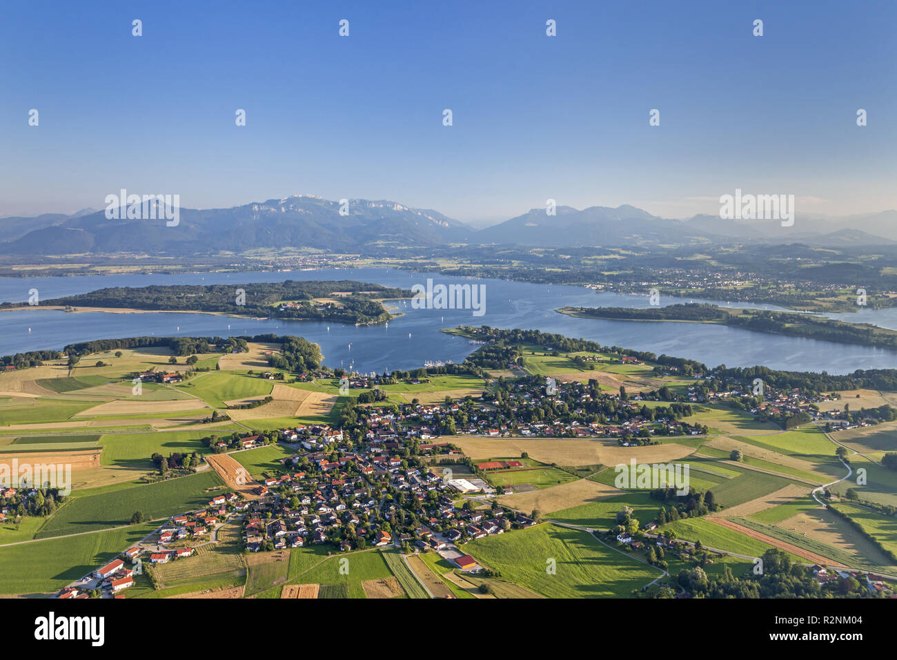 Flight over the Chiemsee with views of Breitbrunn behind the Herreninsel and Chiemgau Alps, Chiemgau, Upper Bavaria, Bavaria, southern Germany, Germany, Europe - Stock Image