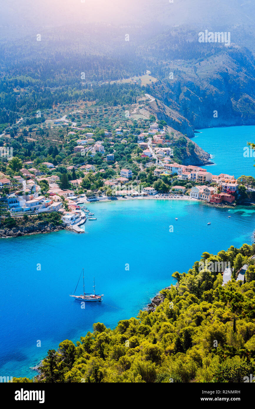 Assos village in morning light, Kefalonia. Greece. White lonely yacht in beautiful turquoise colored bay lagoon water surrounded by pine and cypress trees along the coastline - Stock Image