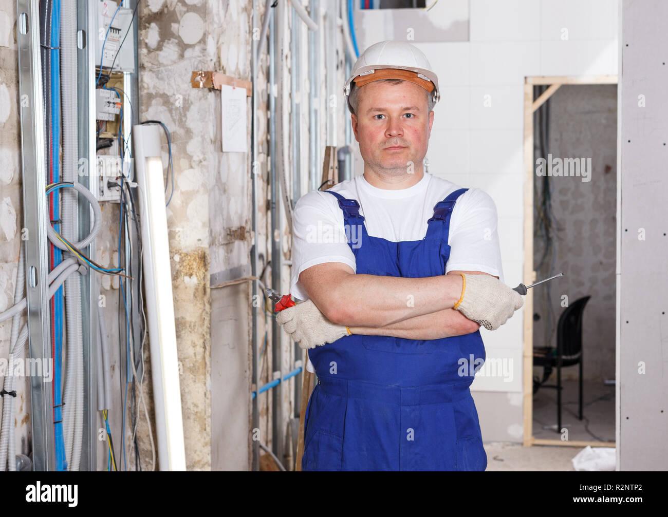 Portrait of confident professional builder posing in repairable room Stock Photo