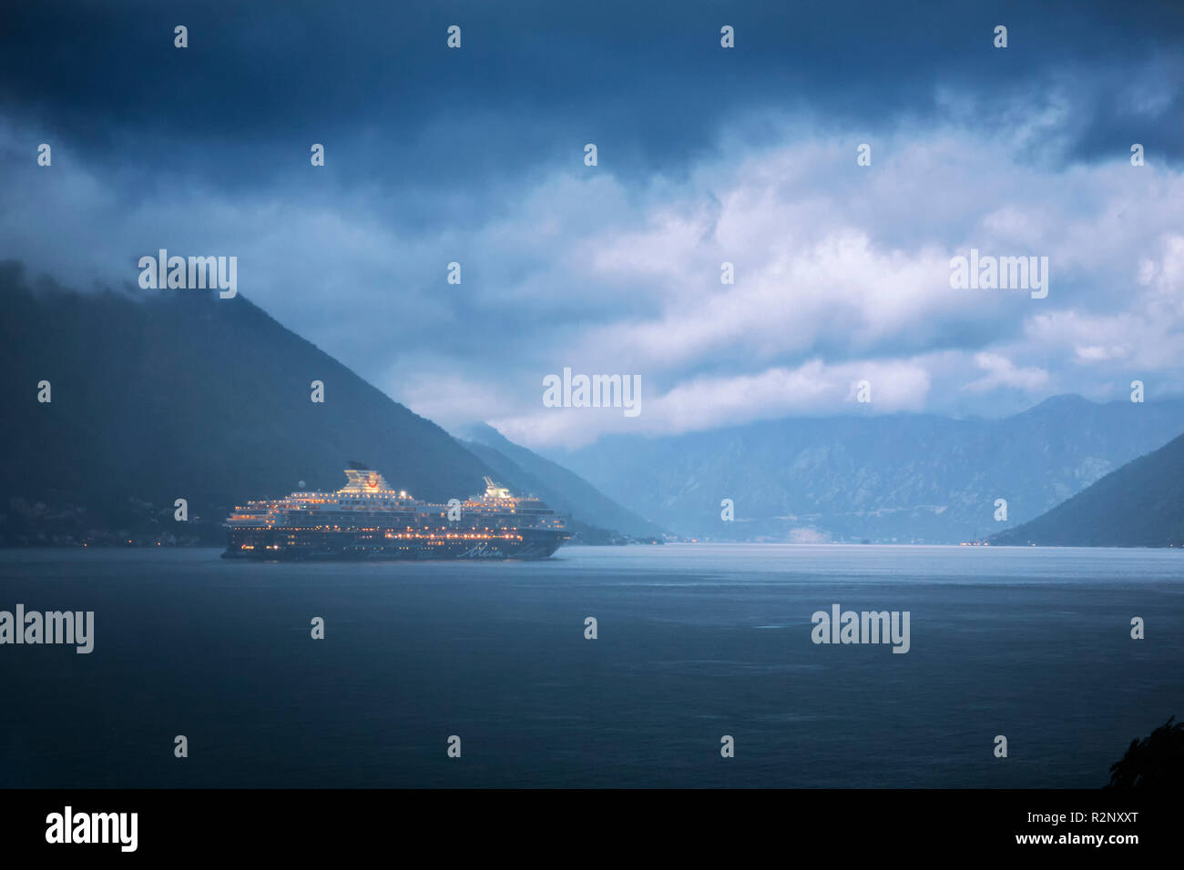 Boka Kotorska (the Bay of Kotor) from the village of Dobrota, Montenegro on a stormy evening: the cruise ship 'Mein Schiff 1' departs for the open sea - Stock Image