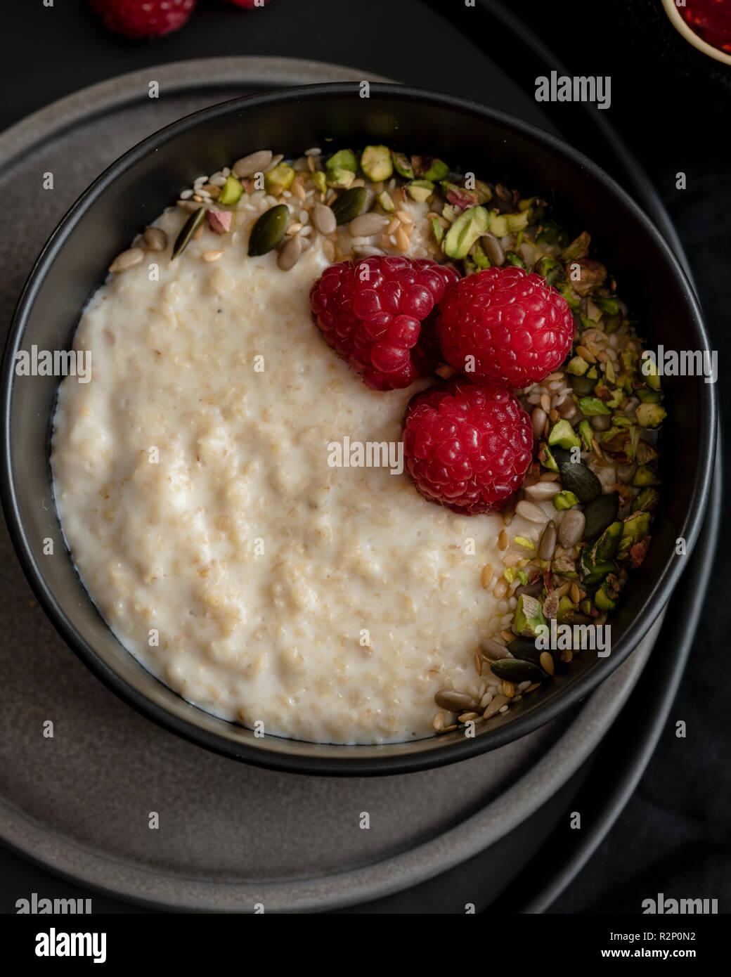 Porridge with fresh raspberries and pistachio nuts - Stock Image