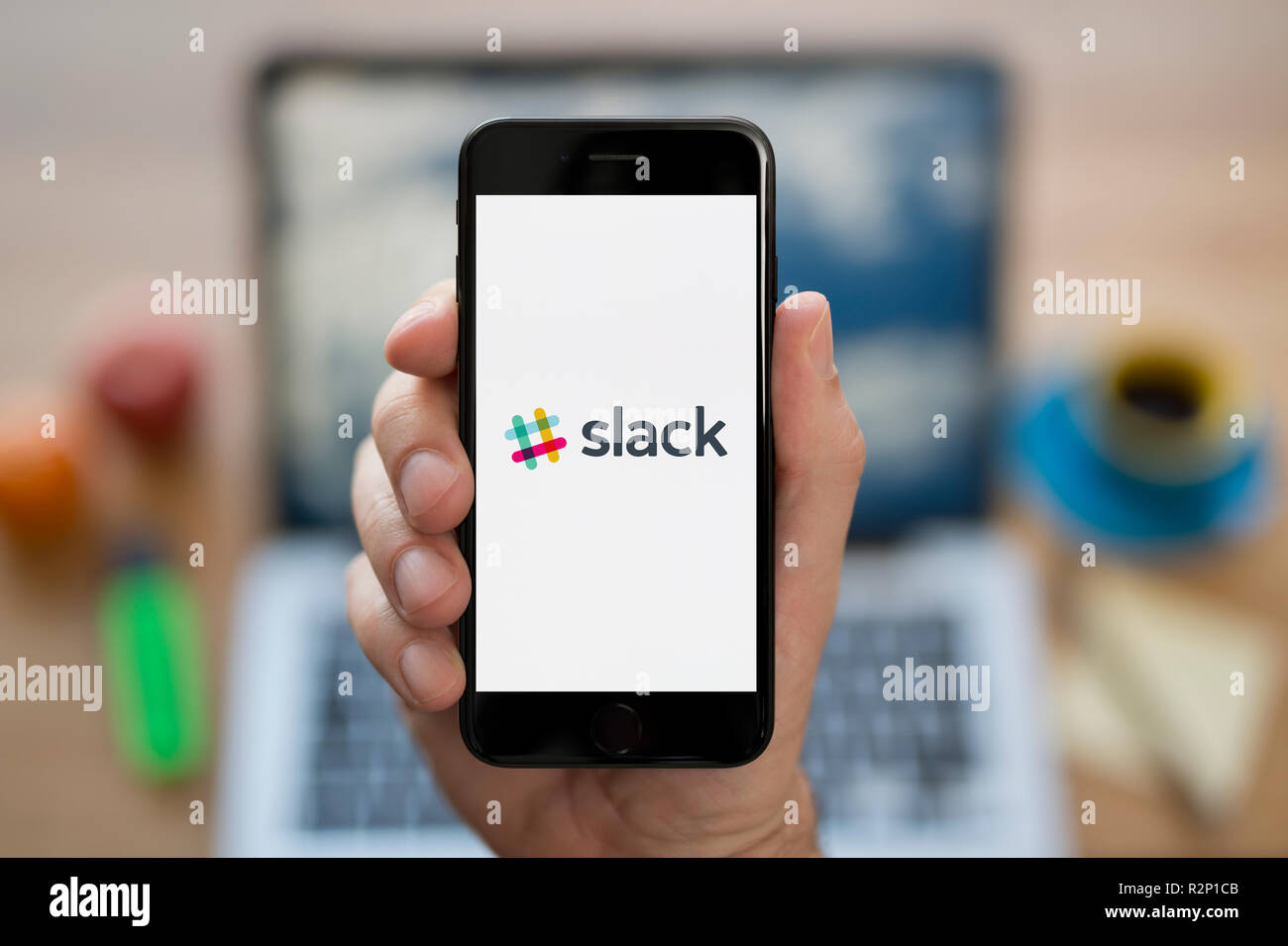 A man looks at his iPhone which displays the Slack logo, while sat at his computer desk (Editorial use only). - Stock Image