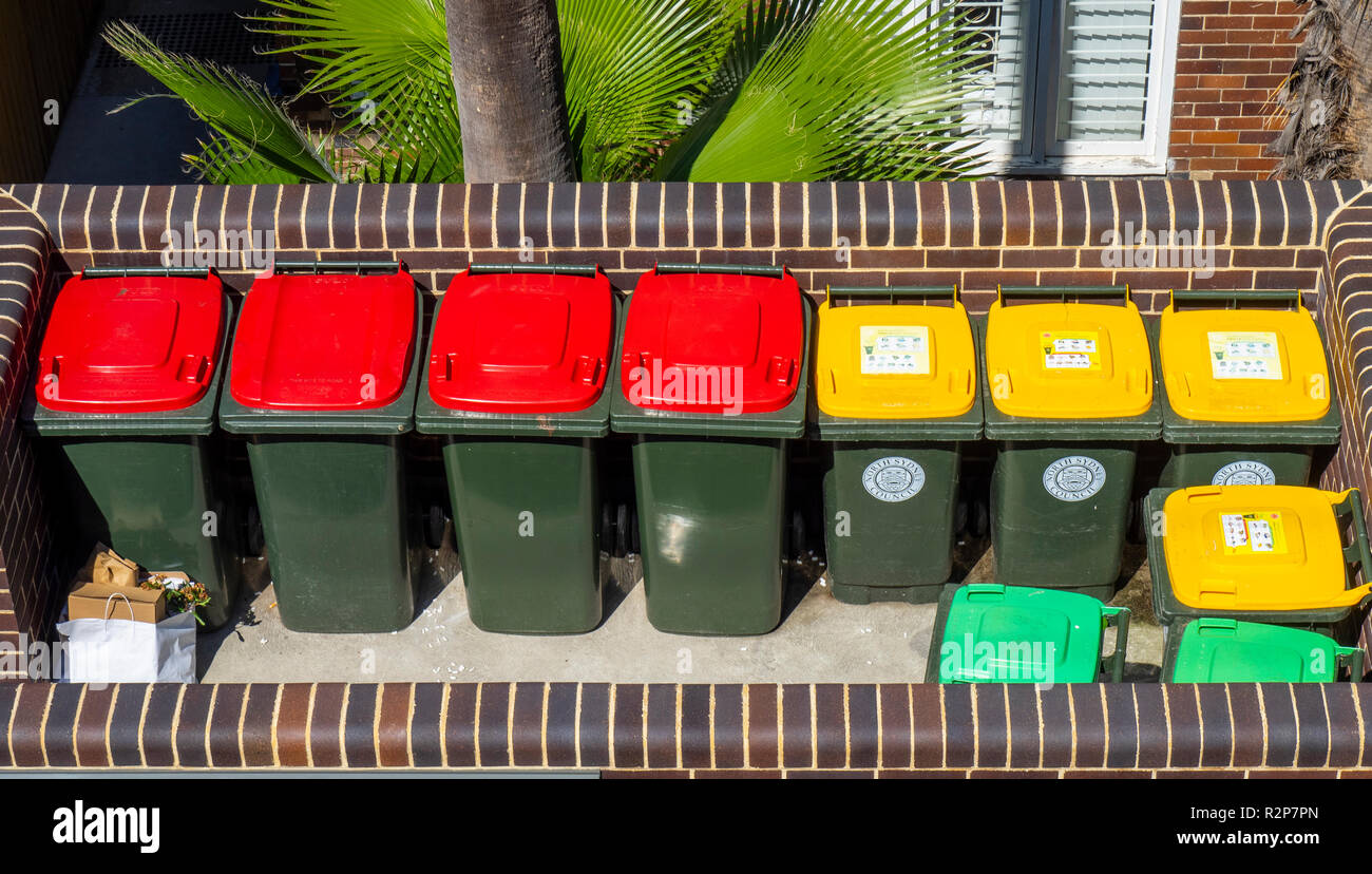 Colour coded rubbish bins, red lid for general trash, yellow lid for recyclable garbage, green lid for garden waste. Stock Photo