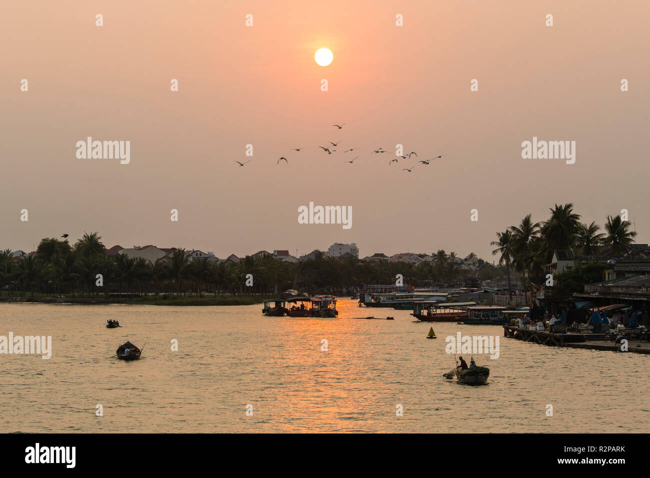 Evening mood, low sun above river in Hoi An, Vietnam, returning fishing boats - Stock Image