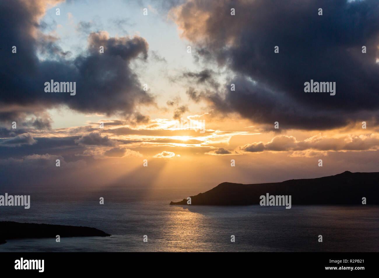 Dramatic sunset between dark storm clouds above Caldera of Santorini - Stock Image