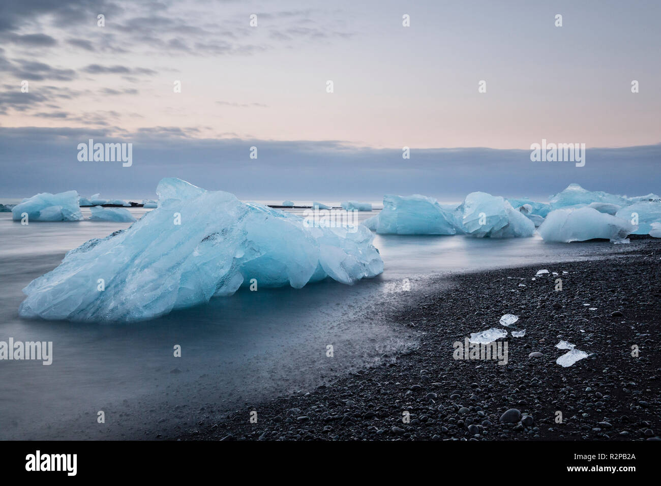 Blue shimmering blocks of ice in blurred water on black beach at Jökulsárlón (Diamond Beach), Iceland, morning mood - Stock Image