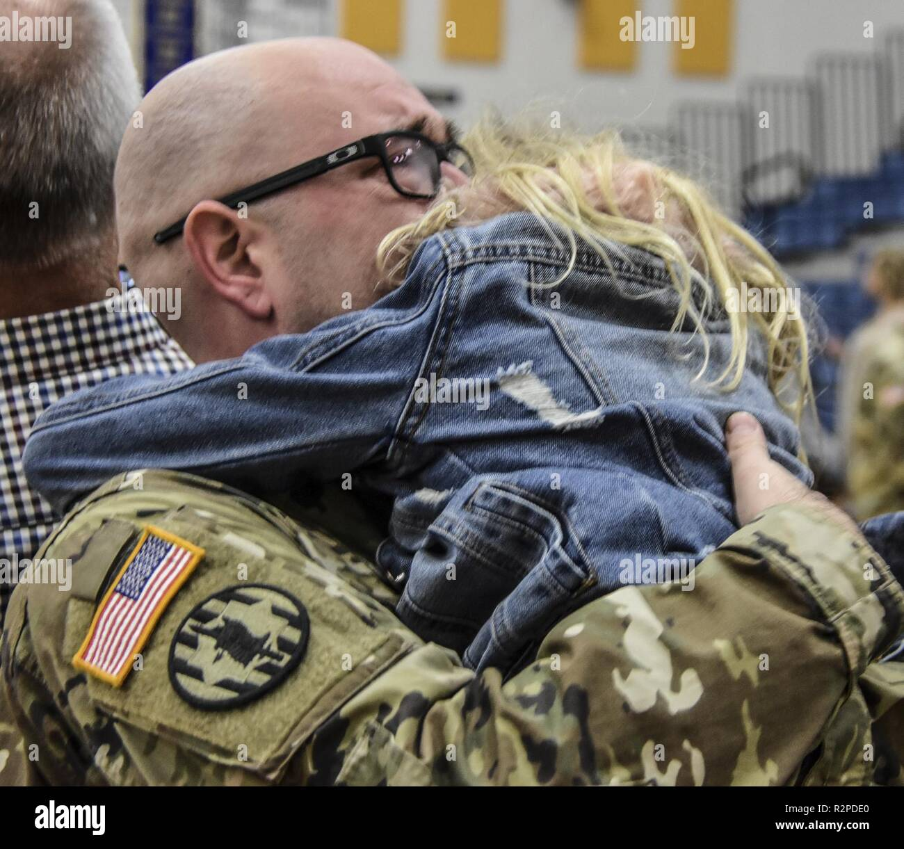 A child embraces her tearful father as they say, 'Good-bye' following a deployment ceremony at DeWitt High School in Michigan.  The Soldier, assigned to the 272nd RSG from the Michigan National Guard is supporting theater level operations in the middle east. - Stock Image