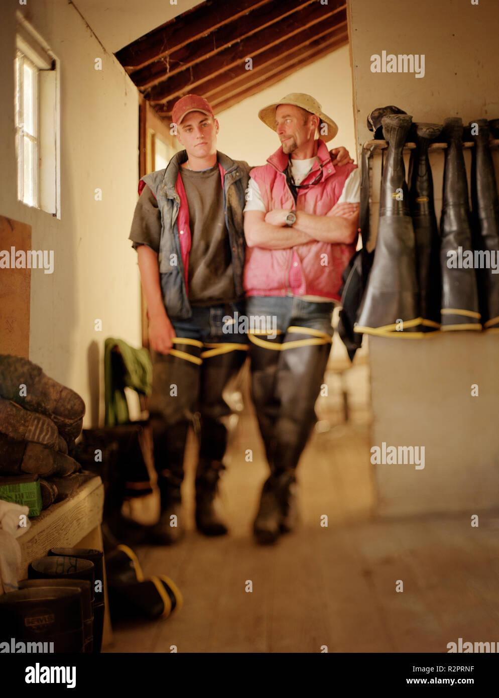 Two men standing together inside a house. - Stock Image