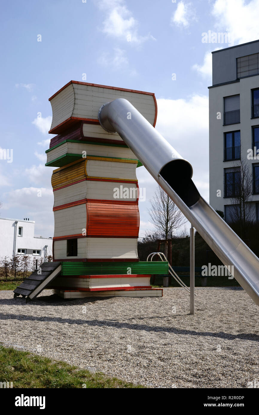 Modern city playground, slide with a ladder modelled on a pile of books, gravel bed - Stock Image