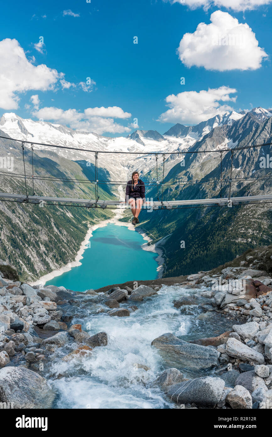 young woman sitting on the suspension bridge near the olperer hut ...