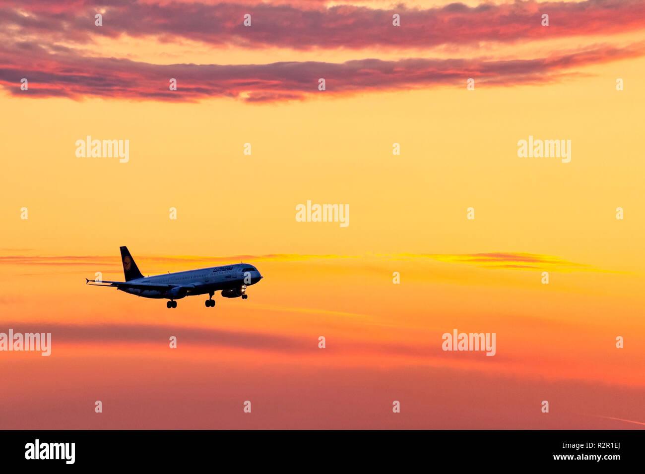 Lufthansa plane preparing landing on Munich Airport during a beautiful sunset. Munich Airport, Flughafen München, Franz Josef Strauss, near Freising / Erding, Erdinger Moos, Oberbayern (Upper Bavaria), Germany - Stock Image