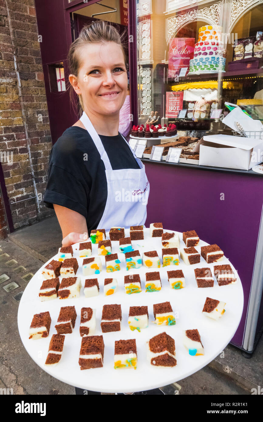 England, London, Southwark, London Bridge City, Borough Market, Cake Shop Sales Girl Offering Free Samples - Stock Image