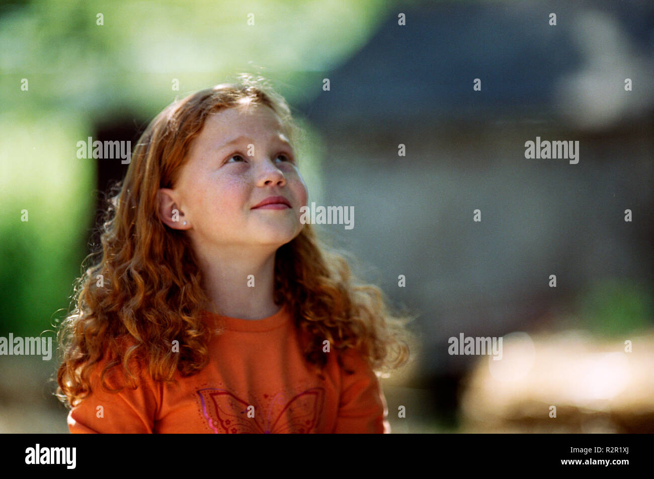 Girl looking up while outside. - Stock Image