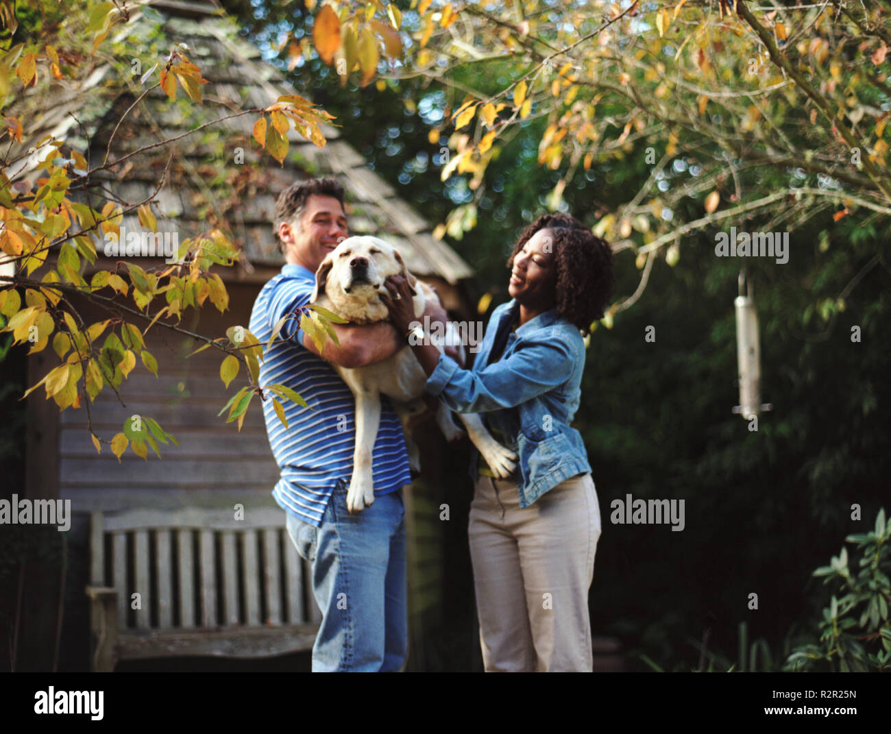 Happy mid-adult couple patting their dog in the back yard of their home. - Stock Image