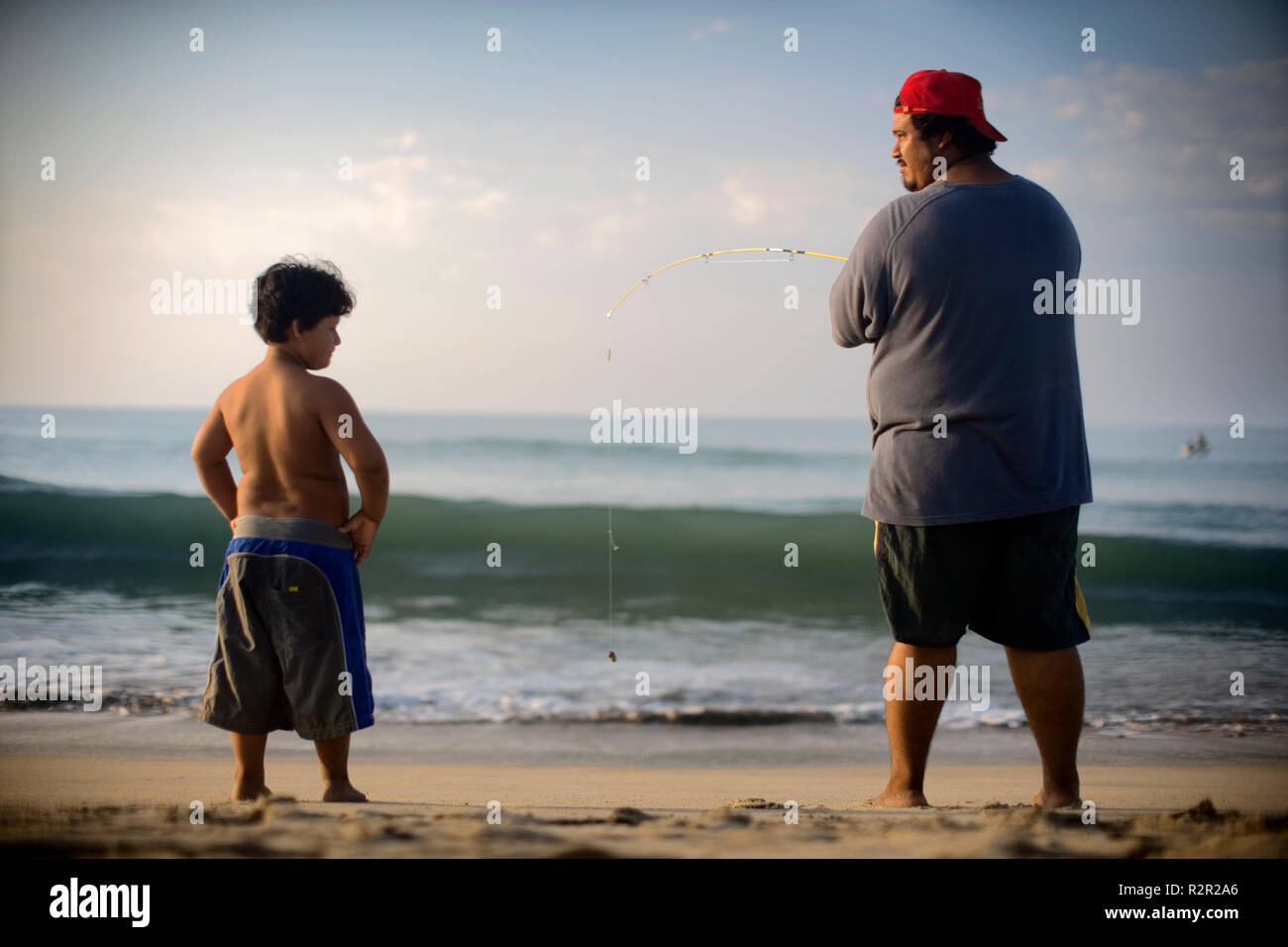 Rear view of a man fishing near the seashore while a small boy looks at him. - Stock Image