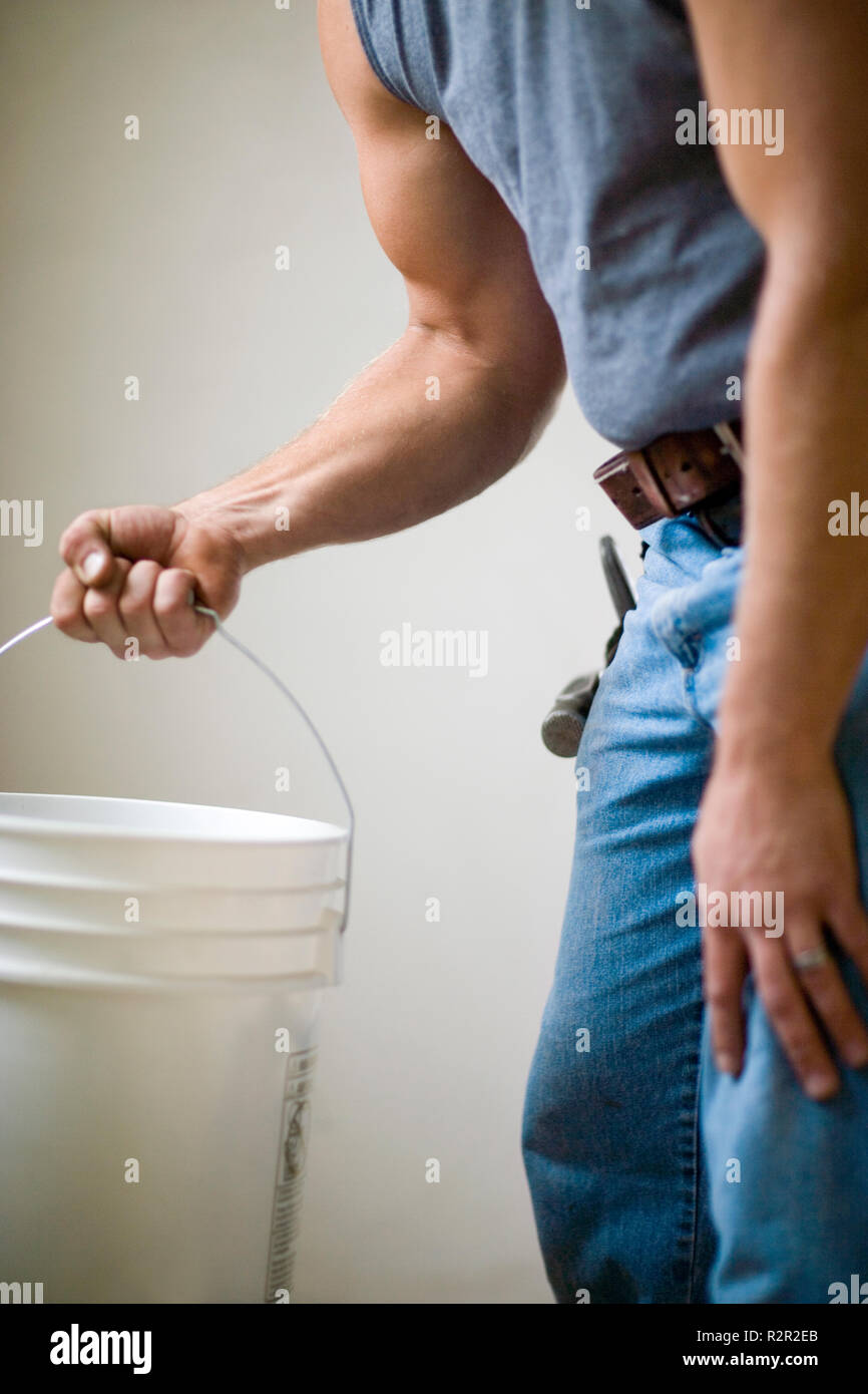 Male builder carrying a white bucket. - Stock Image