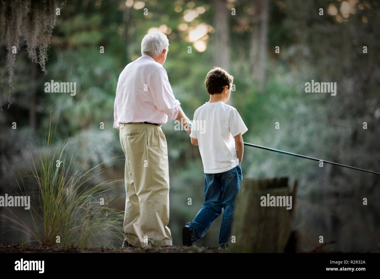 Senior adult man fishing in a lake with his young grandson. - Stock Image