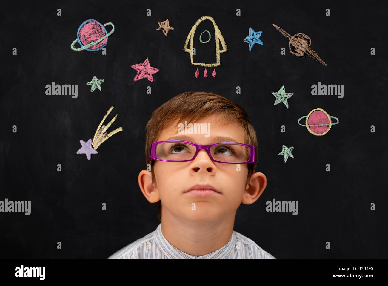 Child imagines the cosmos with blackboard - Stock Image