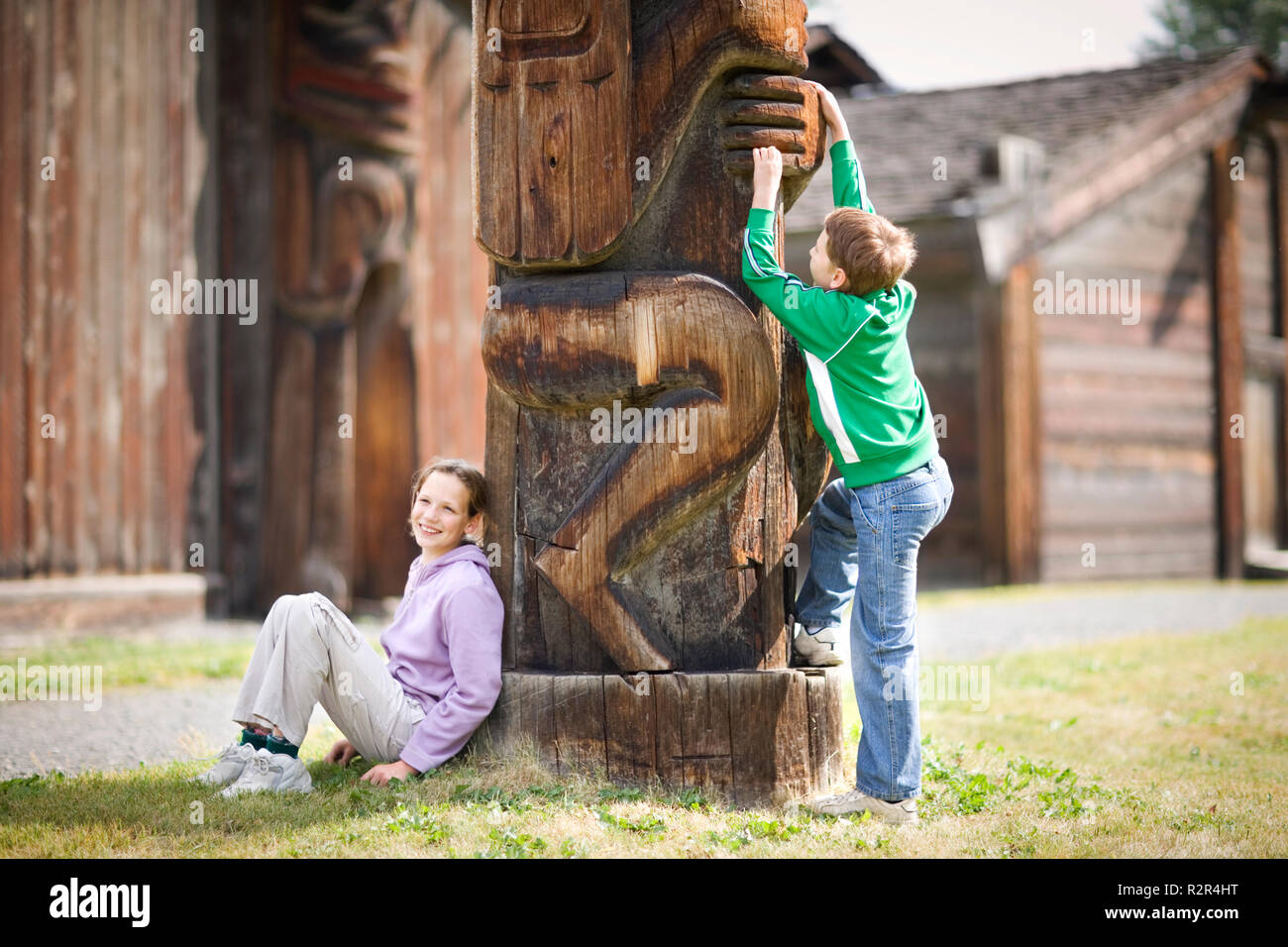 Two children next to a totem pole. - Stock Image