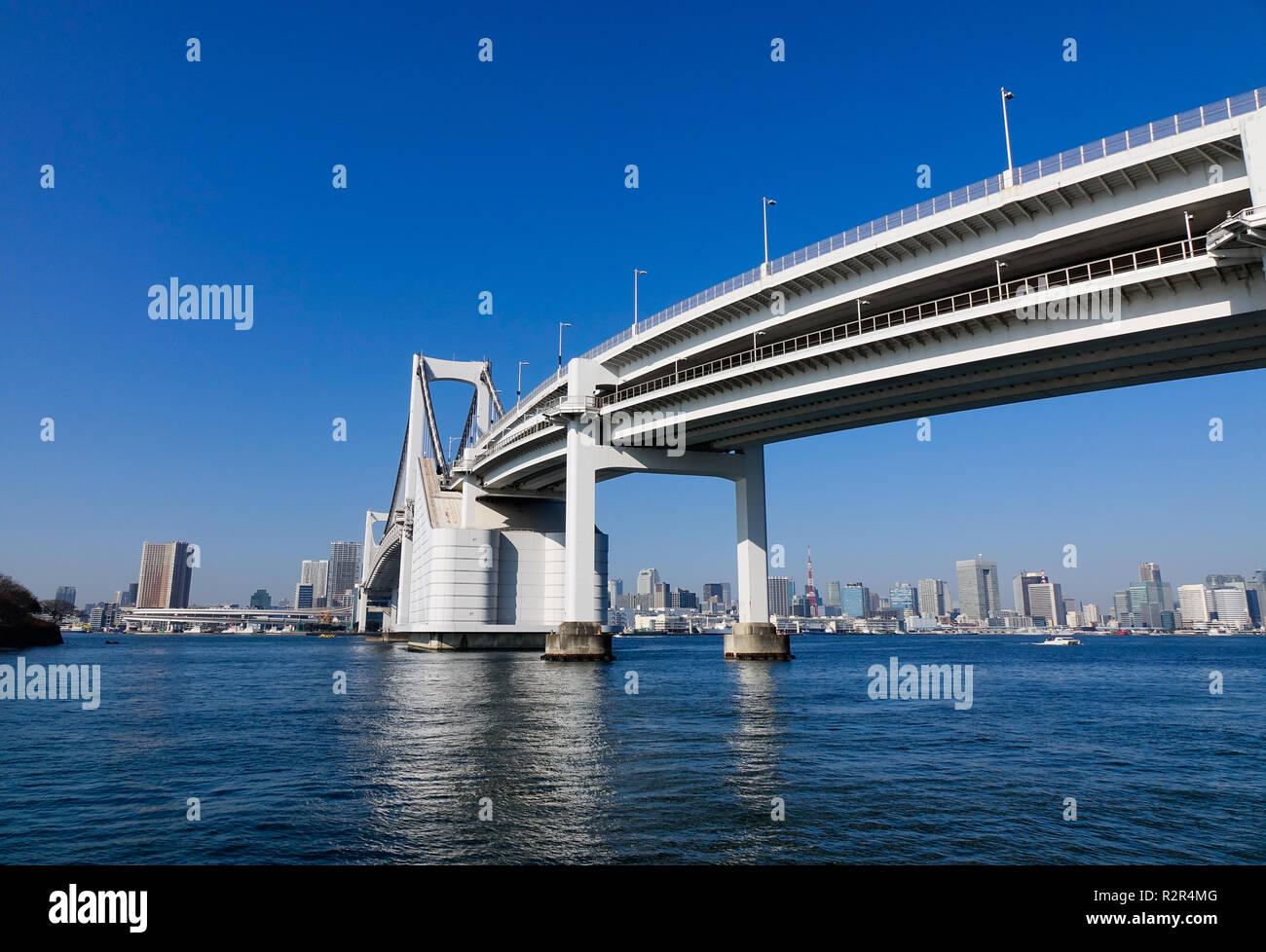 Tokyo, Japan - Jan 4, 2016. Rainbow Bridge and cityscape in Tokyo, Japan. The bridge was built by Kawasaki Heavy Industries, with construction startin Stock Photo