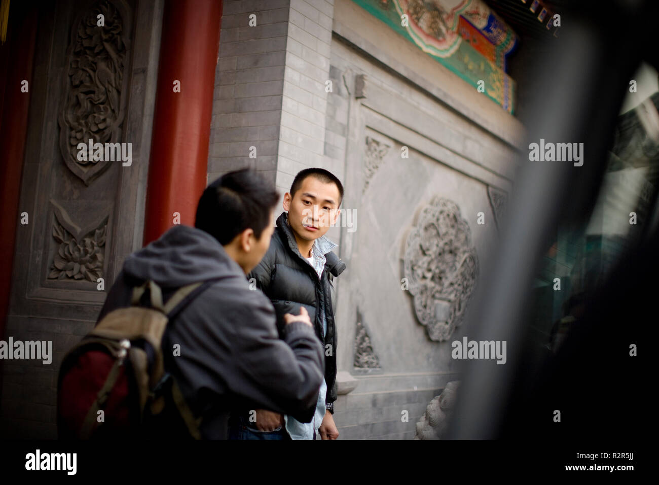 Teenage boy standing with a friend outside school. - Stock Image