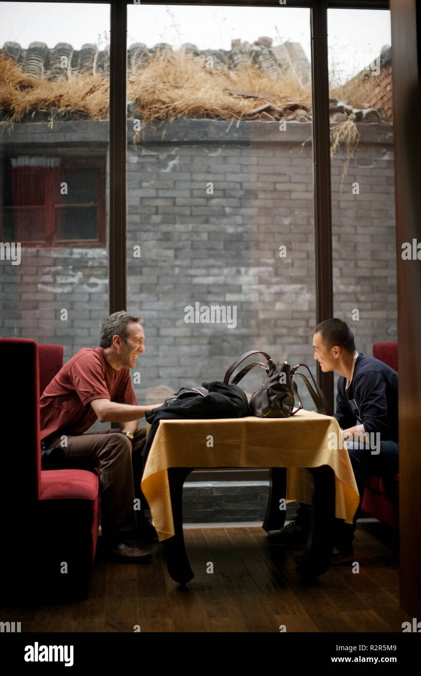 Two mid adult men sitting at a table in a lobby. - Stock Image