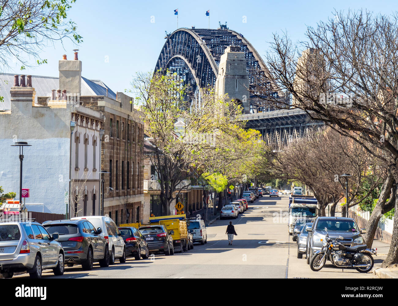 Person walking on Lower Fort Street in Millers Point, Sydney Harboiur Bridge, Sydney NSW Australia. - Stock Image