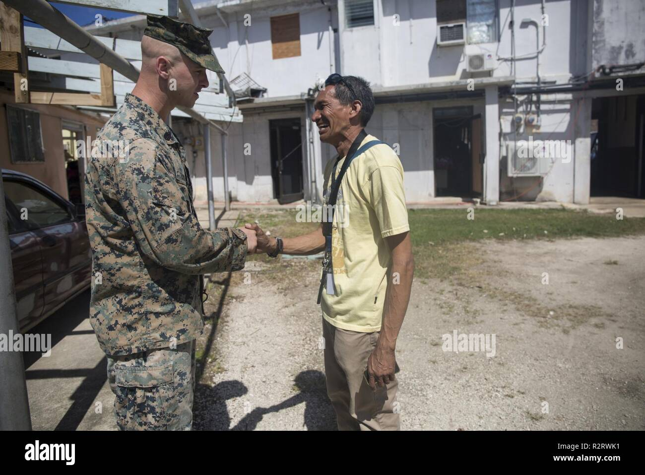 Staff Sgt. Joseph Colvin, an ammunition technician with Combat Logistics Battalion 31, greets a Tinian resident during U.S. Defense Support of Civil Authorities relief efforts on Tinian, Commonwealth of the Northern Mariana Islands, Nov. 6, 2018. Colvin, a native of, Croydon, Pennsylvania, graduated from Bucks County Technical High School in June 2006 before enlisting in August 2007. Businesses, government buildings, homes and schools were heavily damaged by Super Typhoon Yutu, which made a direct hit with devastating effect on Tinian Oct. 25 as the second strongest storm to ever hit U.S. soil - Stock Image
