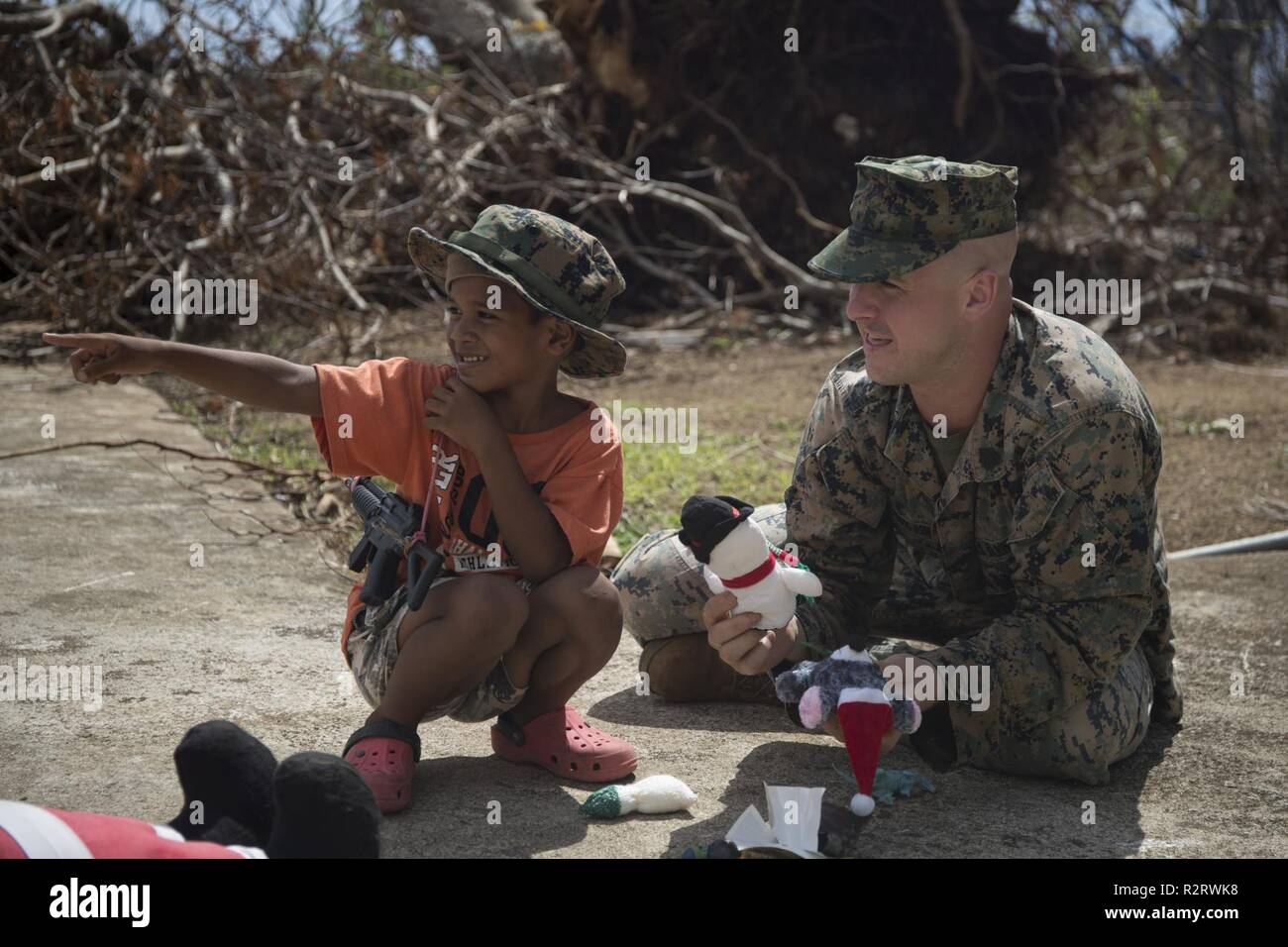 Staff Sgt. Joseph Colvin, an ammunition technician with Combat Logistics Battalion 31, speaks with a Tinian resident during U.S. Defense Support of Civil Authorities relief efforts on Tinian, Commonwealth of the Northern Mariana Islands, Nov. 6, 2018. Colvin, a native of, Croydon, Pennsylvania, graduated from Bucks County Technical High School in June 2006 before enlisting in August 2007. Businesses, government buildings, homes and schools were heavily damaged by Super Typhoon Yutu, which made a direct hit with devastating effect on Tinian Oct. 25 as the second strongest storm to ever hit U.S. - Stock Image