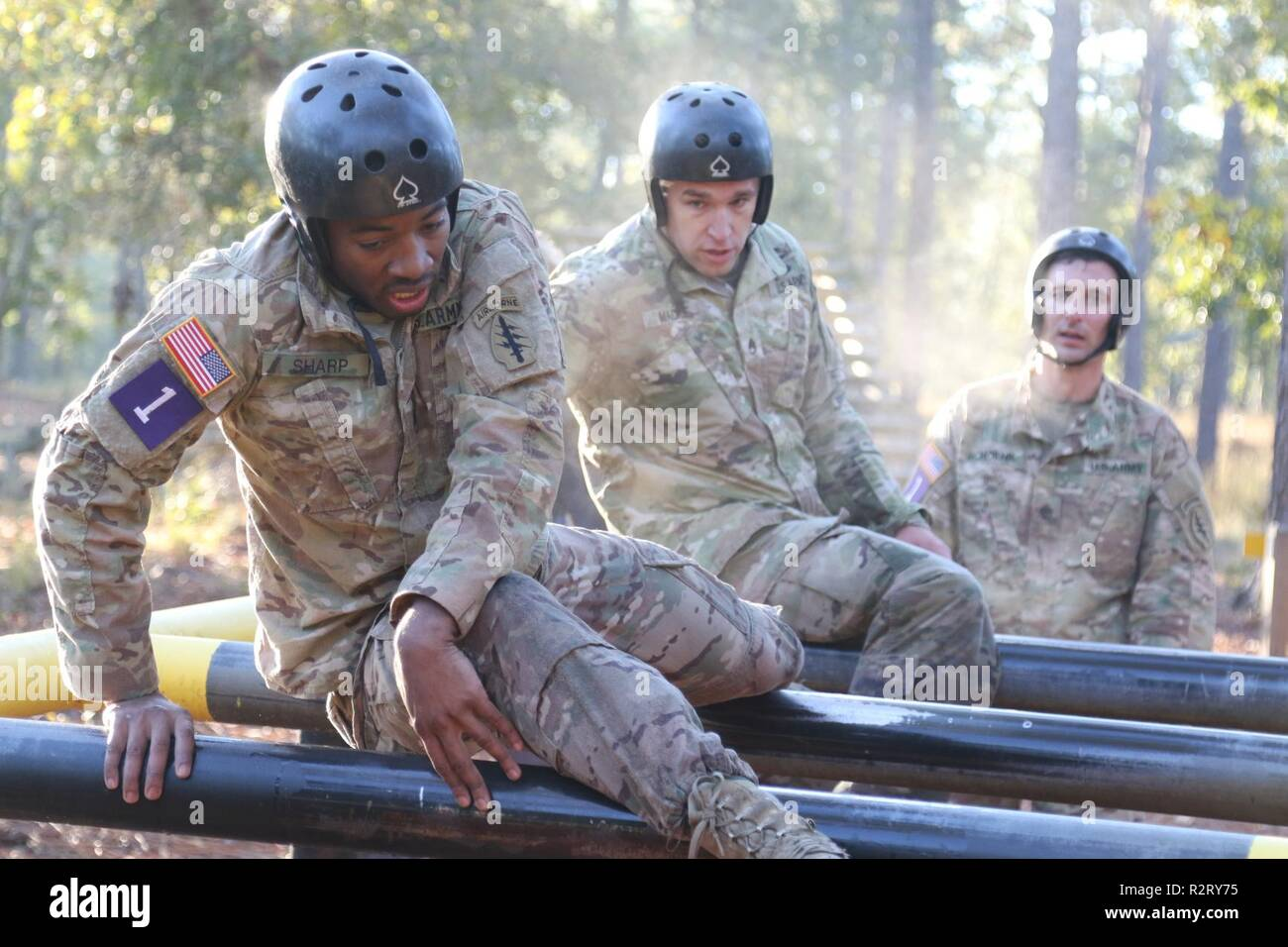 """U.S. Army civil affairs Soldiers assigned to 95th Civil Affairs Brigade (Special Operations) (Airborne), climb over a """"Nasty Nick"""" obstacle during day one of the Best Civil Affairs Team Competition, Oct. 30, 2018, at Camp Mackall, N.C.  Twelve teams from 95th CA Bde. (SO) (A) and U.S. Army John F. Kennedy Special Warfare Center and School, competed in physically and mentally challenging events designed to build camaraderie and esprit de corps among Soldiers.  Teams competed in either the Civil Affairs Team or Enhancement MOS Team category. The events included the """"Nasty Nick"""" Obstacle Course,  Stock Photo"""