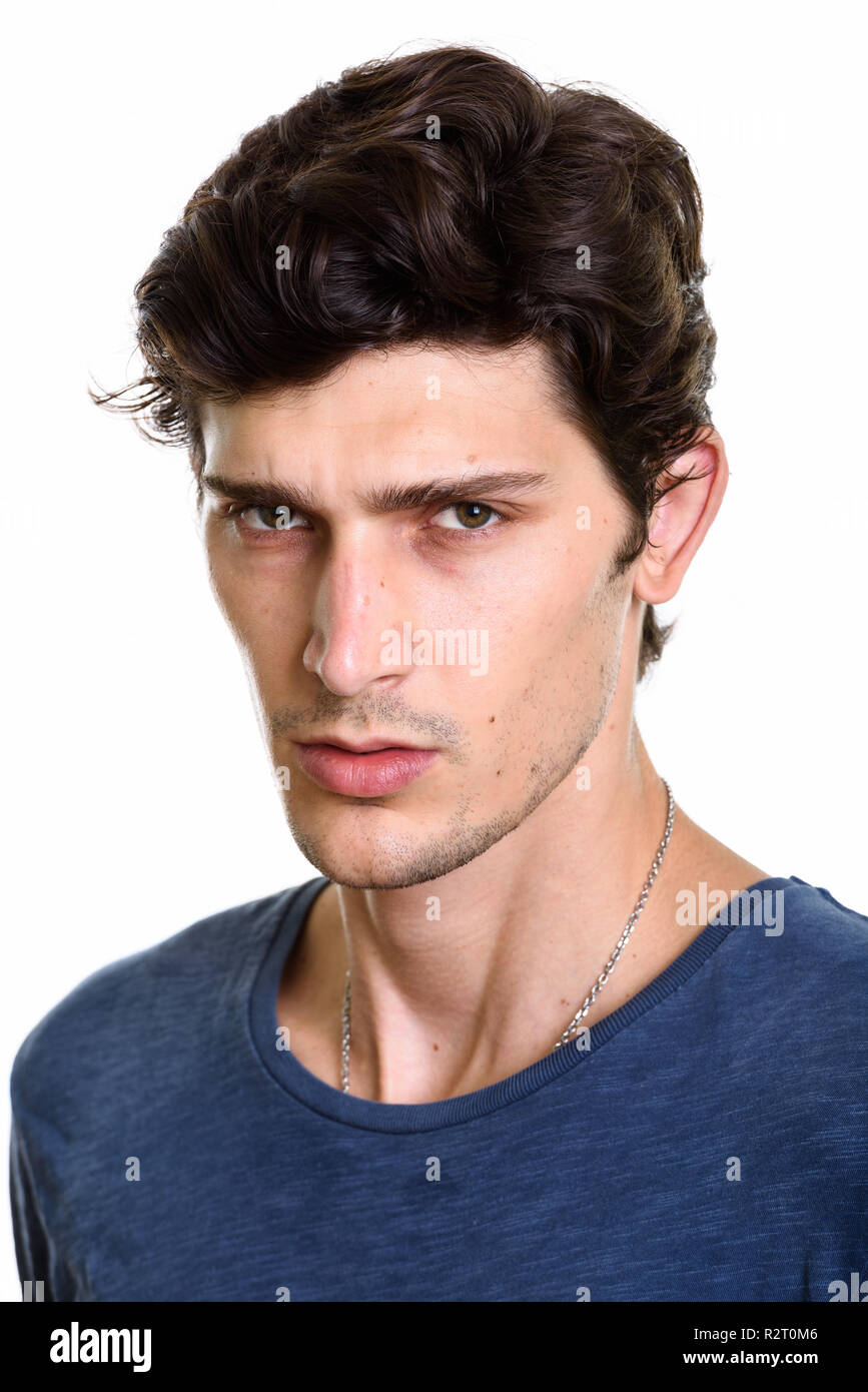 Face of young handsome man looking angry - Stock Image
