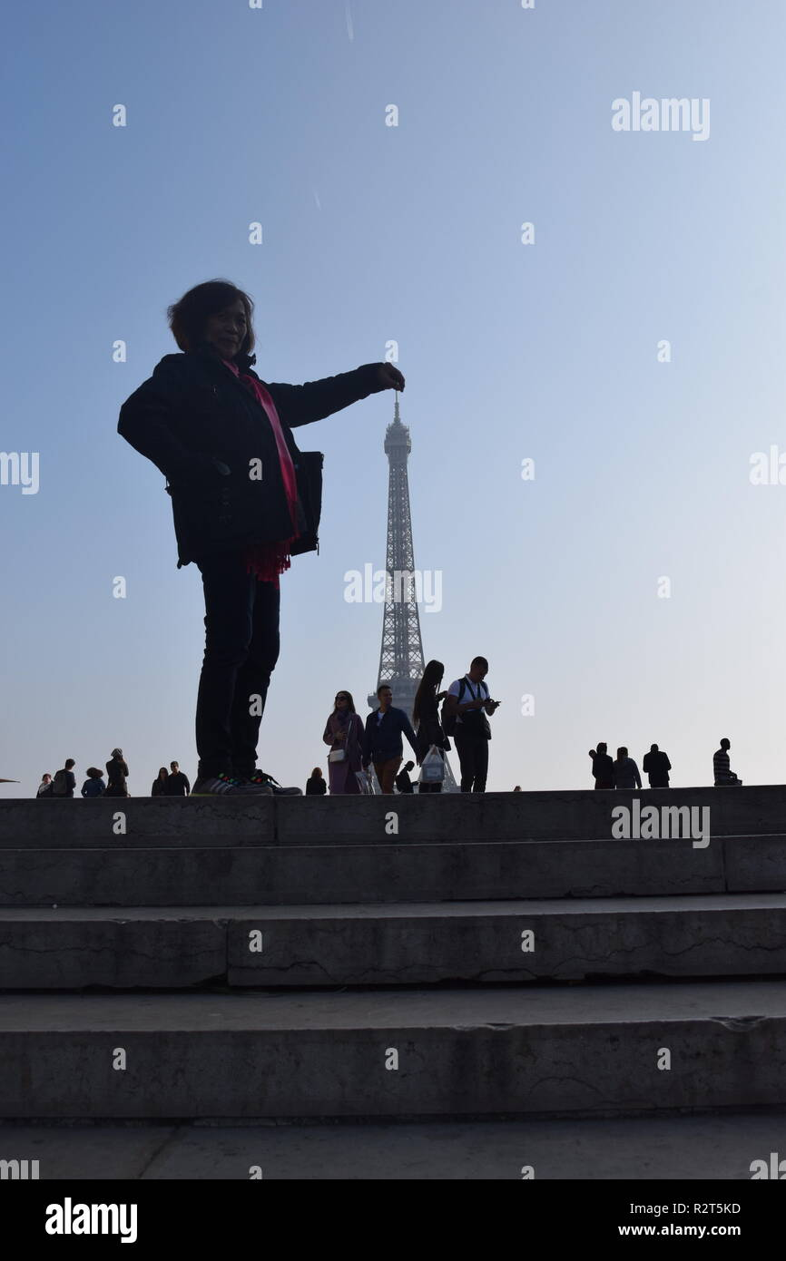 Silhouettes of a tourists pose for pictures with the Eiffel Tower in the background at the Trocadero Paris, France - Stock Image