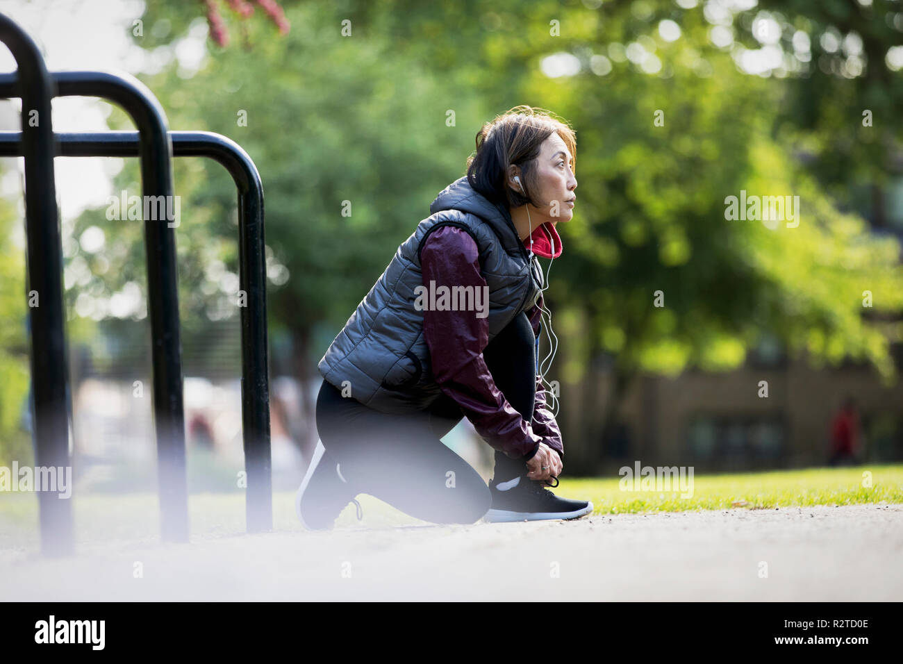 Active senior female runner with headphones tying shoe in park - Stock Image