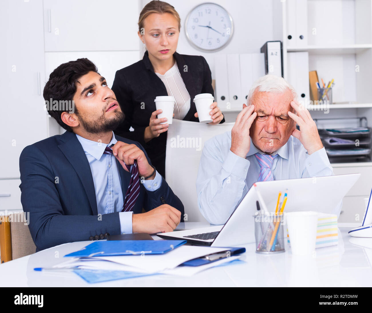 Mature boss is having complicated issue with reports made by subordinates in office. - Stock Image