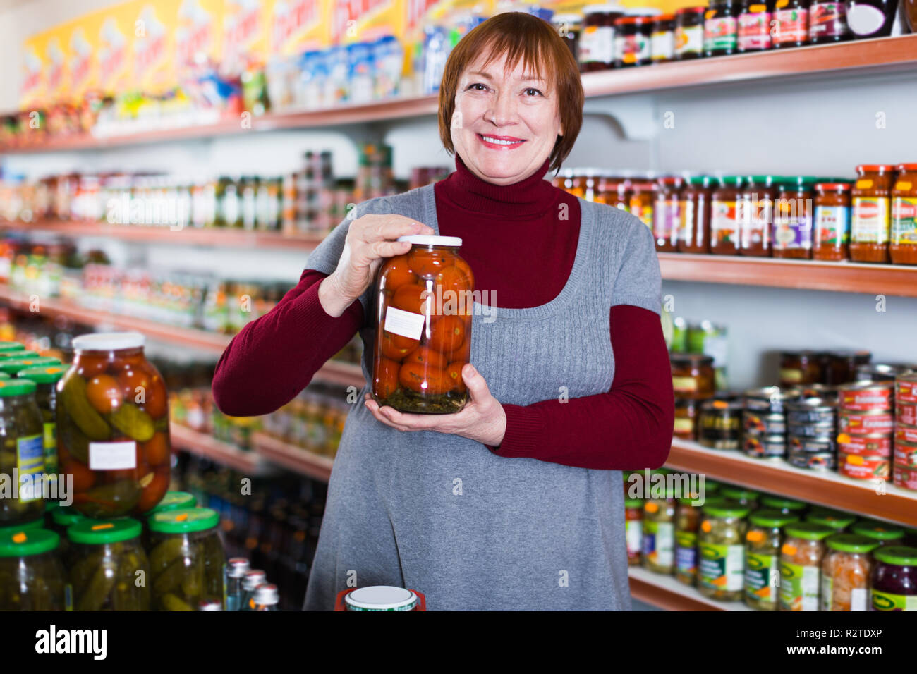 Mature female in the store holding preserved food of tomatoes - Stock Image
