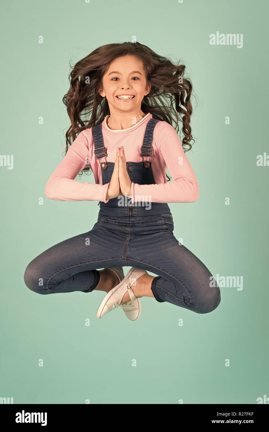 Girl in jeans overall jump in yoga pose on blue background. Meditation, concentration, zen concept. Fashion, beauty, look. Energy, energetic, activity pilates sport - Stock Image