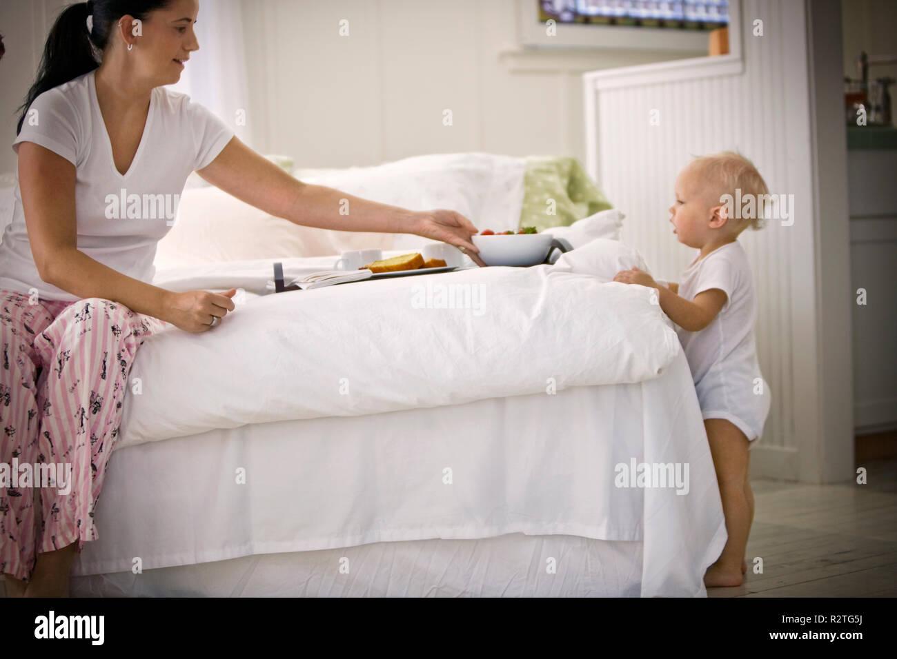 Mid-adult woman sitting on a bed with breakfast while her toddler son looks on. - Stock Image