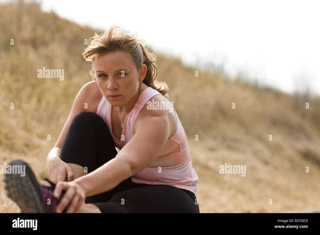Portrait of a teenage girl sitting stretching while in a field. Stock Photo