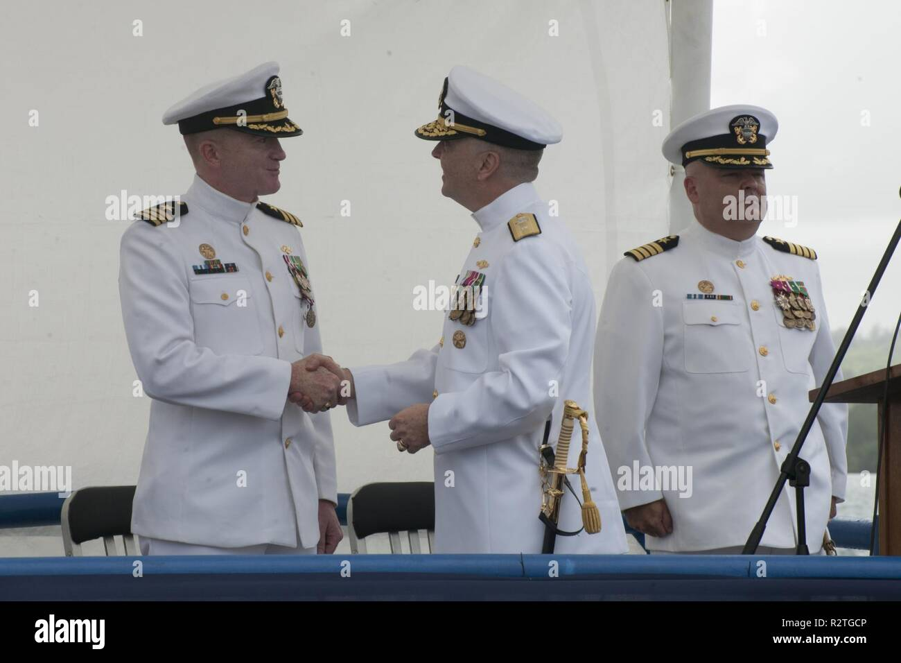 PITI, Guam (Nov. 9, 2018) Rear Adm. James Waters, III, director, Maritime Headquarters, U.S. Pacific Fleet, ceneter, congratulates Cmdr. Thomas O'Donnell, left, on a job well done during a change of command ceremony aboard Los Angeles-class attack submarine USS Oklahoma City (SSN 723), Nov. 9. Oklahoma City is one of four Guam-homeported submarines assigned to SUBRON 15. - Stock Image