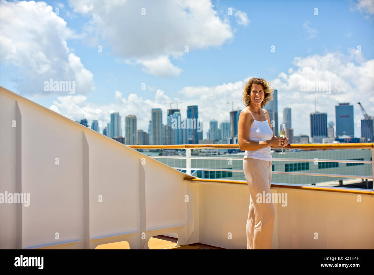 Middle aged woman standing on deck of cruise ship. Stock Photo