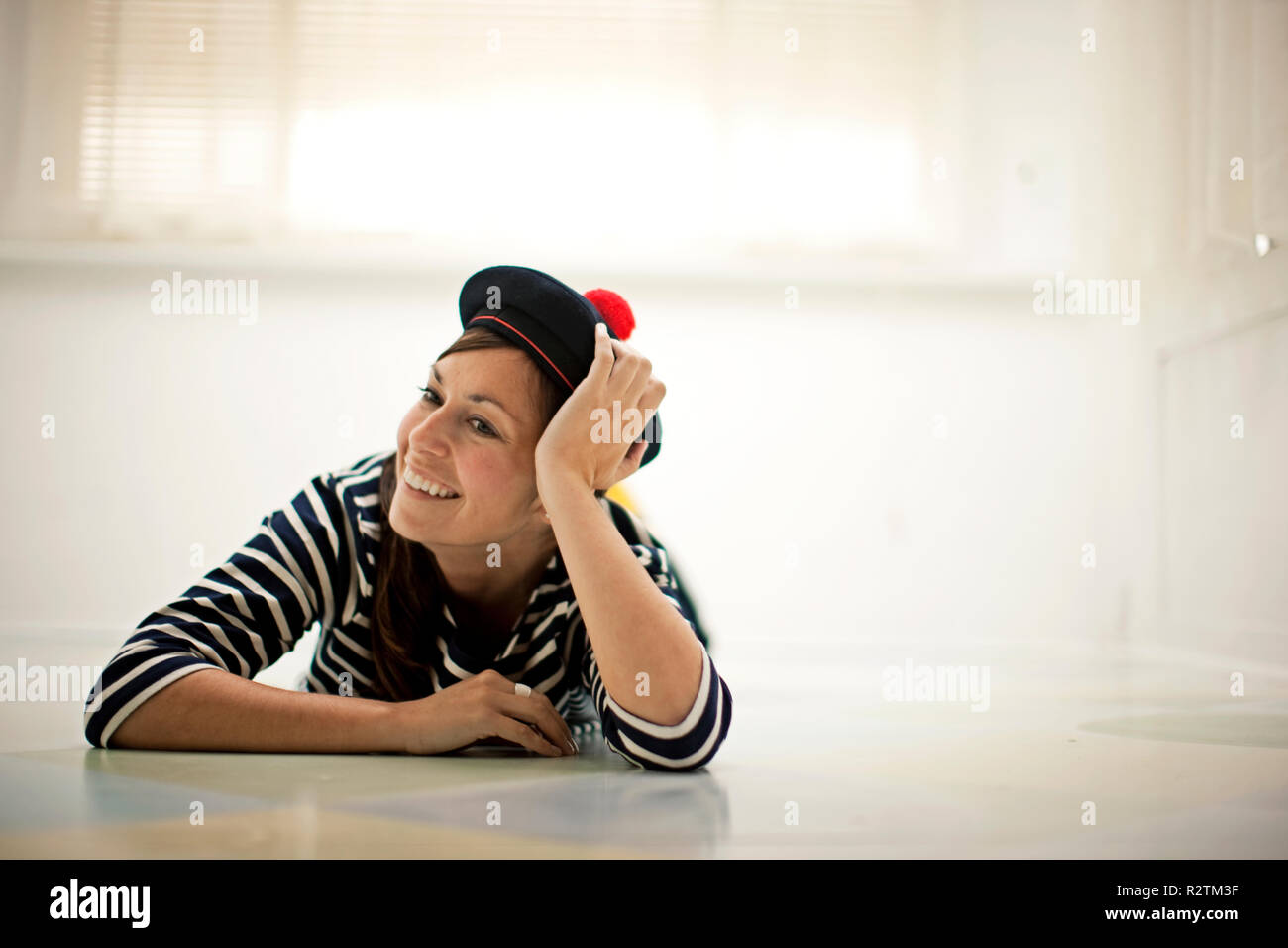 Woman lying on the floor wearing a Balmoral bonnet and smiling Stock Photo
