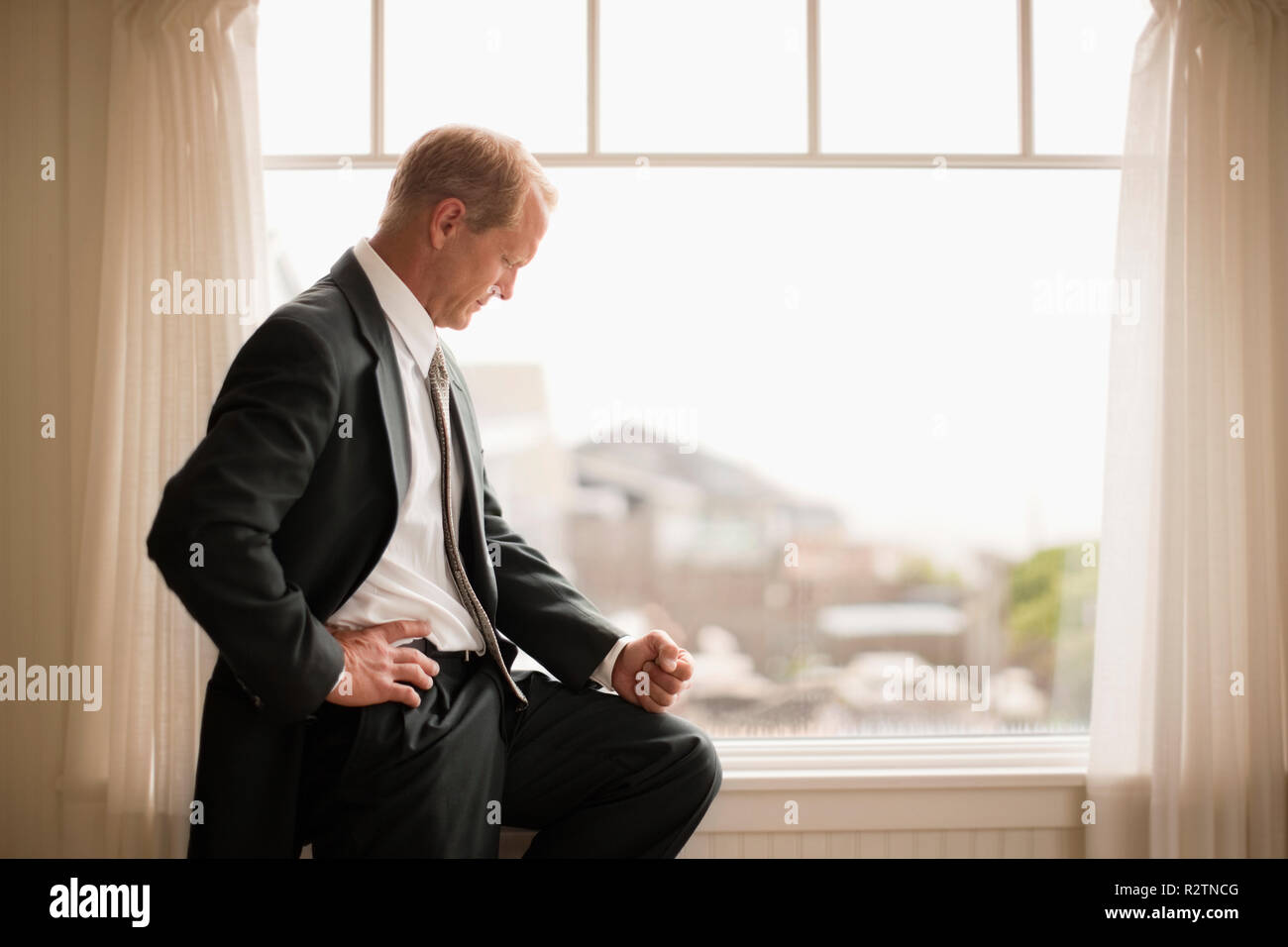 Businessman looking out window deep in thought Stock Photo