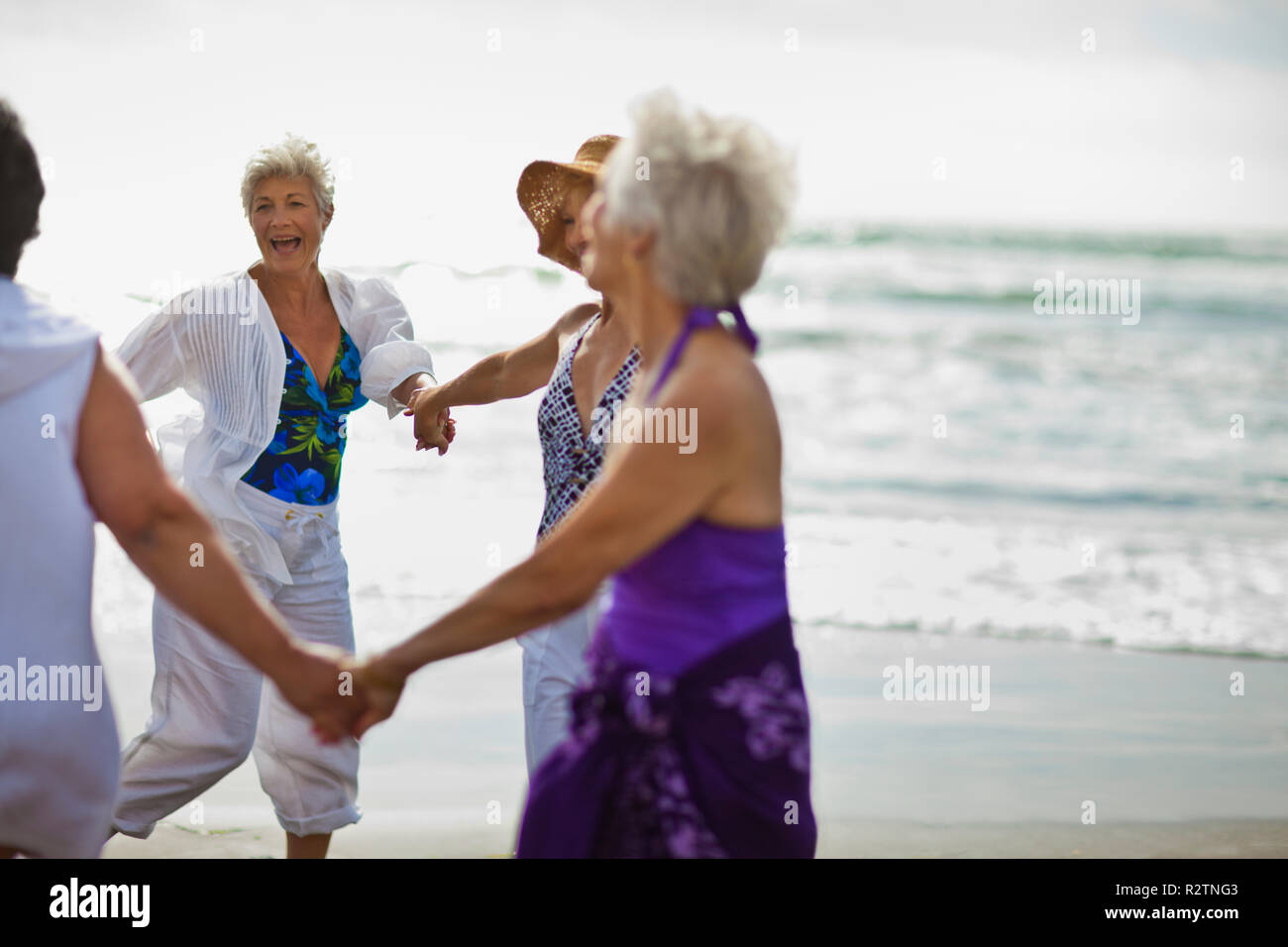 Happy mature friends enjoying a day at the beach. - Stock Image