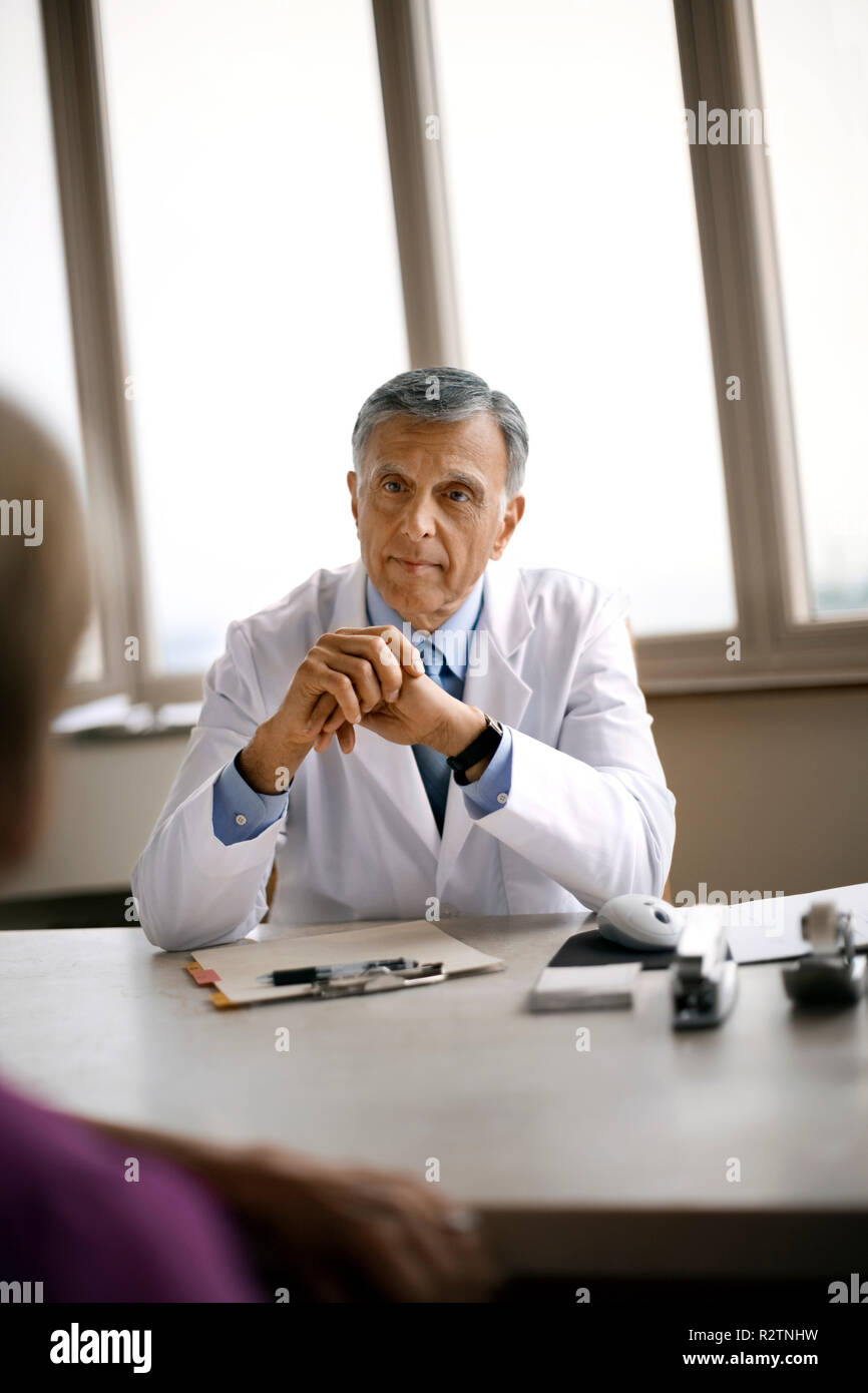 Friendly senior doctor conversing with a mature patient. - Stock Image