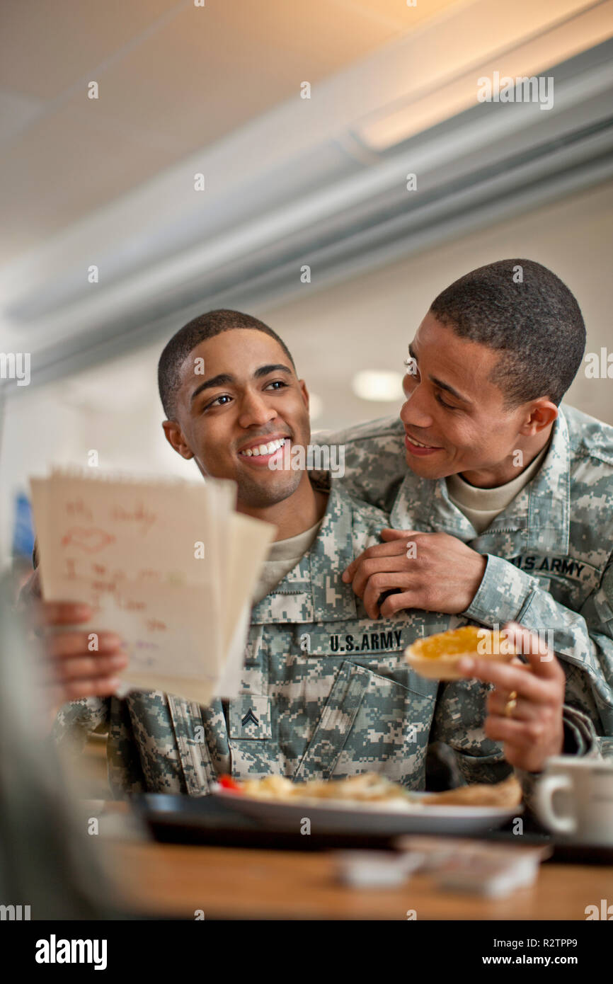 Young soldier looks over his friend's shoulder as he reads a  letter during breakfast. - Stock Image